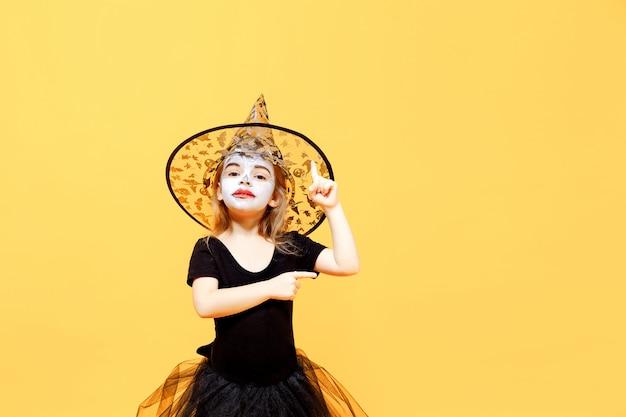 Pequena menina sendo bruxa pensativa no halloween
