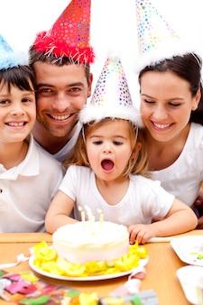 Pequena menina soprando velas no dia de seu aniversário