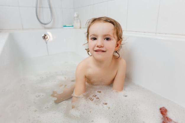 Pequena menina tomando banho com espuma na banheira.
