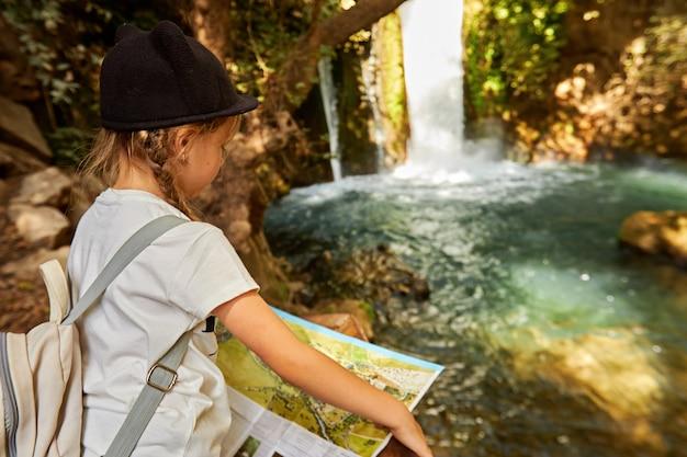 Pequena menina turista lendo o mapa na floresta em dia de sol perto da cachoeira