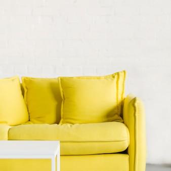 Pequena mesa branca na frente do sofá amarelo contra a parede de tijolos brancos