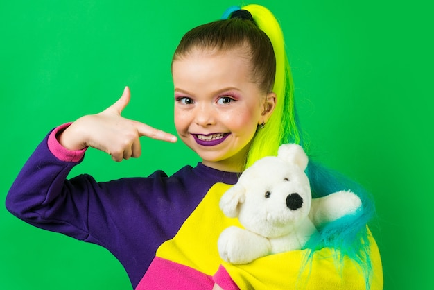 Pequena modelo com cabelos coloridos abraçando e apontando no urso de pelúcia