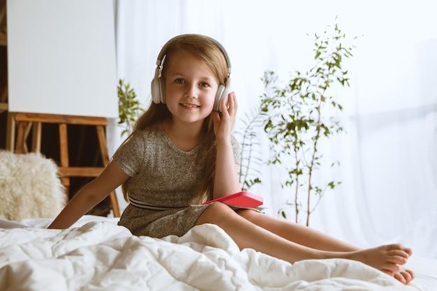 Pequena modelo sentada em sua cama com grandes fones de ouvido, ouvindo suas músicas favoritas e curtindo.