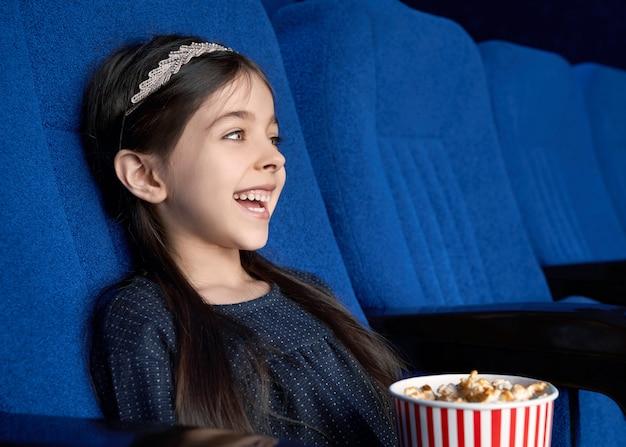 Pequena morena assistindo comédia e rindo no cinema