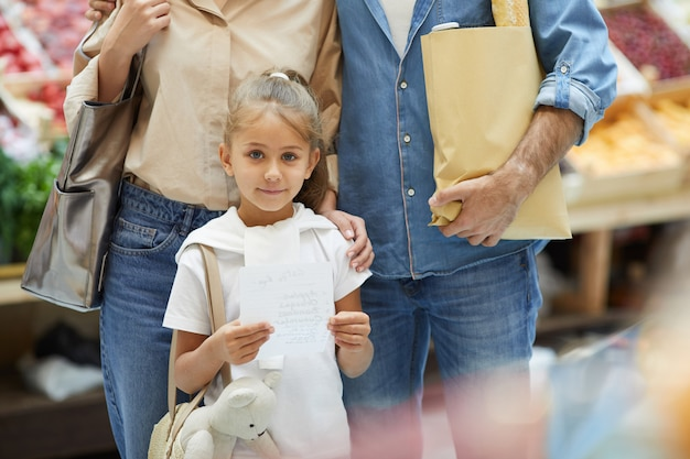 Pequena mulher com os pais no supermercado