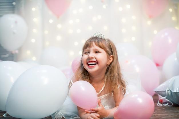 Pequena mulher, em roupas festivas e tiara, senta-se contra balões