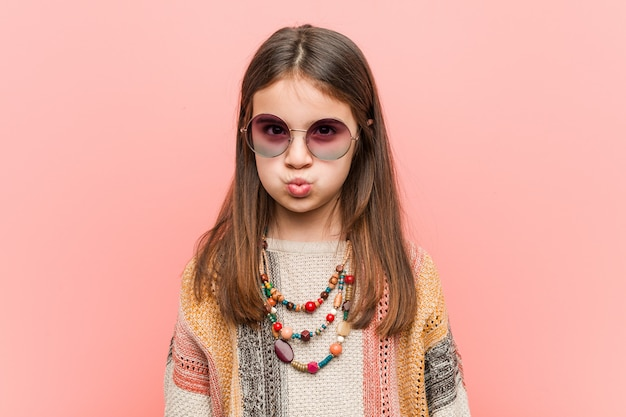 Pequena mulher hippie sopra bochechas, tem expressão cansada. conceito de expressão facial.