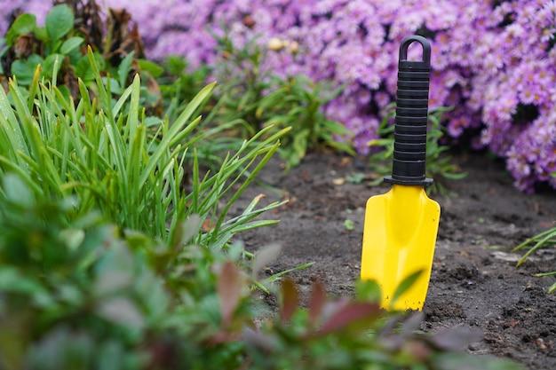 Pequena pá amarela presa no chão em um jardim