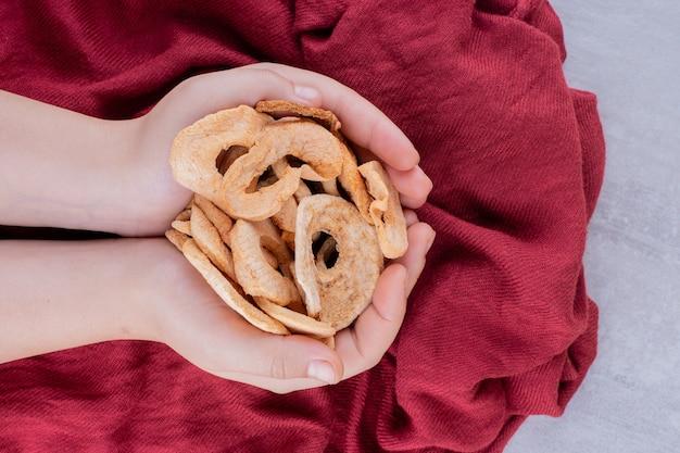 Pequena pilha de fatias de maçã secas, mantidas nas mãos em concha sobre fundo branco.