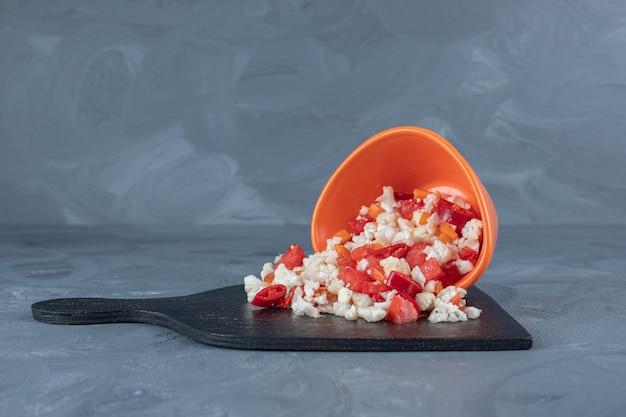 Pequena pilha de salada de couve-flor e pimenta e uma tigela em um quadro negro sobre fundo de mármore.