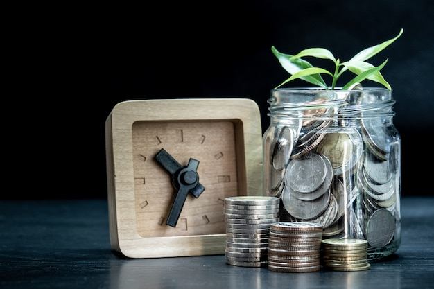 Pequena planta da parte superior da moeda em frasco transparente com pequeno relógio de madeira