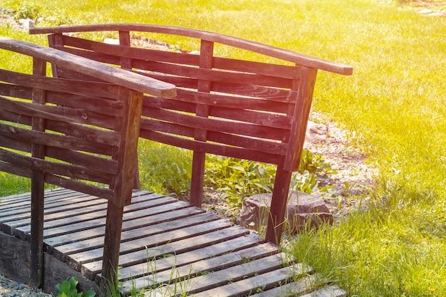 Pequena ponte de madeira em um belo jardim verde.
