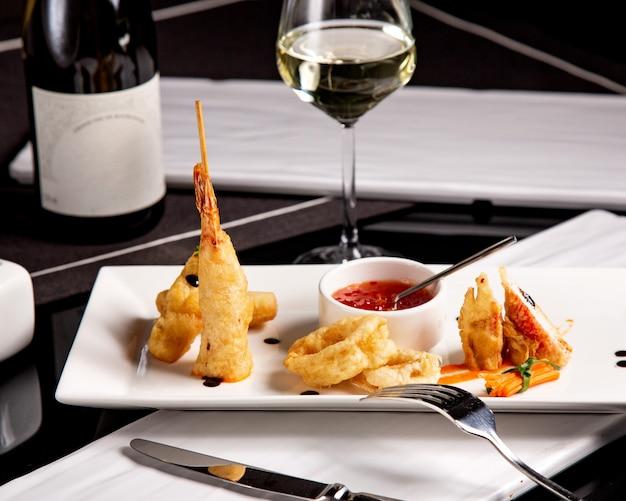 Pequena porção de entradas de frutos do mar com camarão frito crocante de lula e molho de pimentão doce