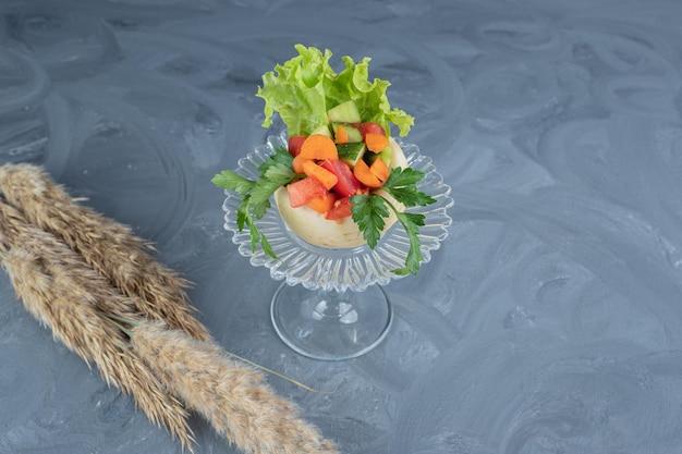 Pequena porção de vegetais picados em cima de um nabo branco em um pedestal de vidro com hastes de grama na mesa de mármore.