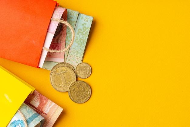 Pequena sacola vermelha com moeda ucraniana hryvnia com copyspace amarelo