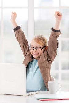 Pequena senhora de negócios. menina bonitinha de óculos e trajes formais sentada à mesa e usando o laptop