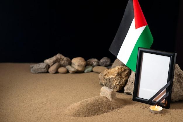 Pequena sepultura com bandeira palestina e pedras na mesa escura morte na guerra da palestina