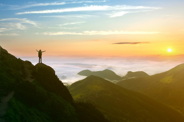 Pequena silhueta de homem alpinista apreciando o belo nascer do sol pela manhã