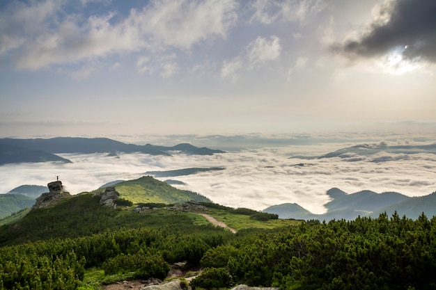 Pequena silhueta de turista com os braços erguidos na formação rochosa no vale da montanha cheia de nuvens brancas inchadas e neblina e coberta com encostas de montanhas sempre verdes da floresta sob o céu claro