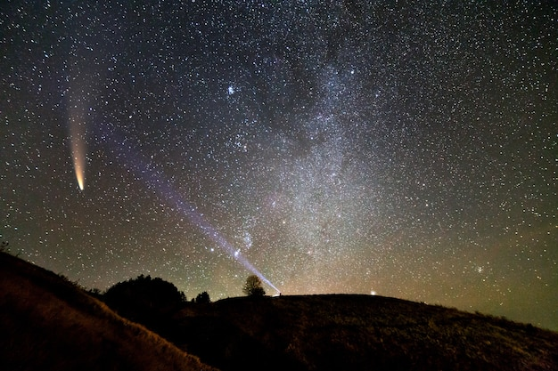Pequena silhueta de um cientista com lanterna na cabeça apontando feixe de luz brilhante no céu