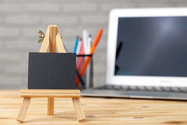 Pequena tela preta em um suporte de madeira na mesa de trabalho