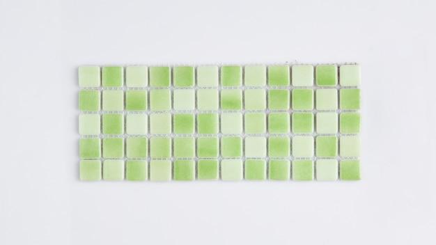 Pequena telha cerâmica verde sobre fundo branco, vista superior, faiança. para o catálogo