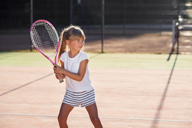 Pequena tenista em uniforme branco, concentrando-se e concentrando-se no treinamento antes do jogo. fundo de luz solar.