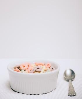 Pequena tigela branca de loops de cereal de pequeno-almoço e colher contra o pano de fundo branco