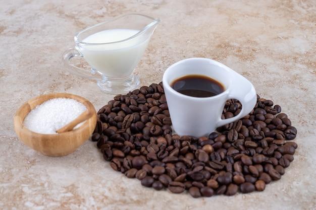 Pequena tigela de açúcar ao lado de uma pilha de grãos de café em torno de uma xícara de café