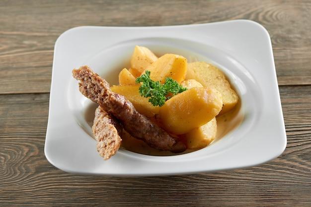 Pequena tigela de restaurante servida com rodelas douradas de batata frita, linguiça fina e decorada com folhas de salsa. parece muito delicioso e nutritivo.