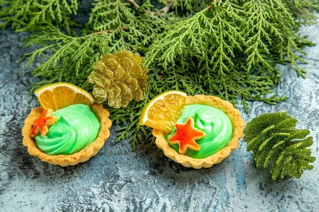 Pequena torta de vista inferior com ramos verdes de pinho creme pasteleiro na superfície cinza