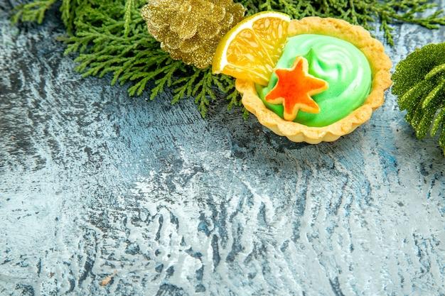 Pequena torta de vista inferior com ramos verdes de pinho em uma superfície cinza espaço livre