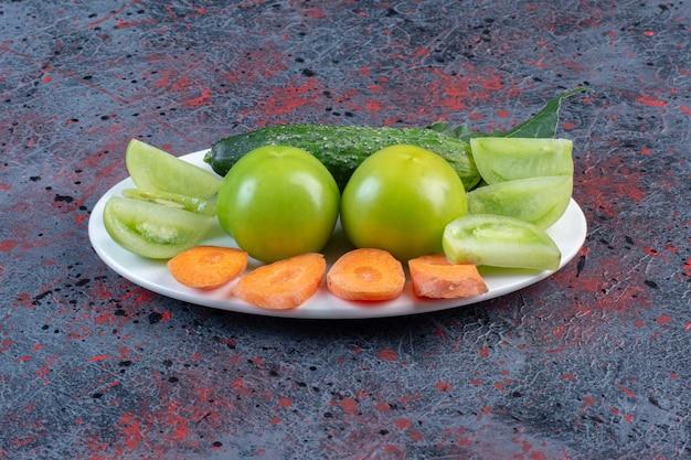 Pequena variedade de vegetais em uma travessa em fundo de cor escura. foto de alta qualidade