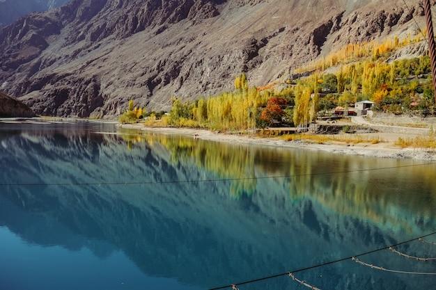Pequena vila com vista para o reflexo na água do lago khalti