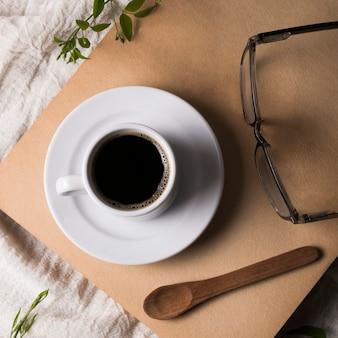Pequena xícara de café no prato e óculos de leitura