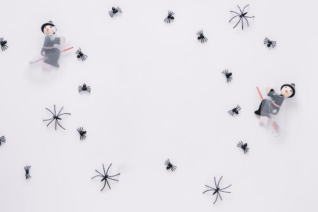 Pequenas aranhas e bruxas decorativas colocadas em círculo