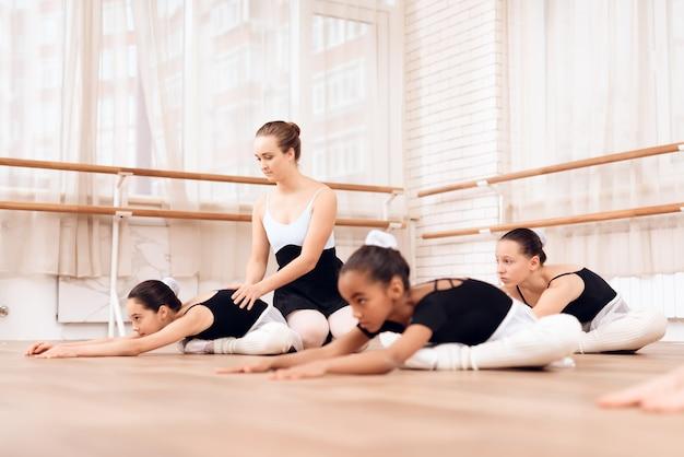 Pequenas bailarinas praticam no salão de balé.