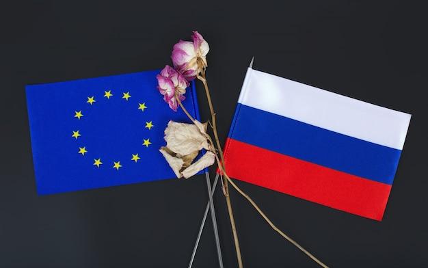 Pequenas bandeiras da união europeia e da federação russa e duas flores secas em uma superfície preta. fundo