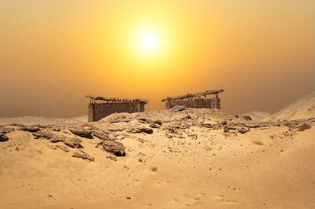 Pequenas cabanas no meio do deserto com um fundo de paisagem incrível cabana de pedra do deserto