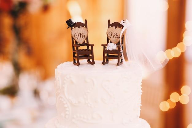 Pequenas cadeiras de balanço decoradas com acessórios de recém-casados