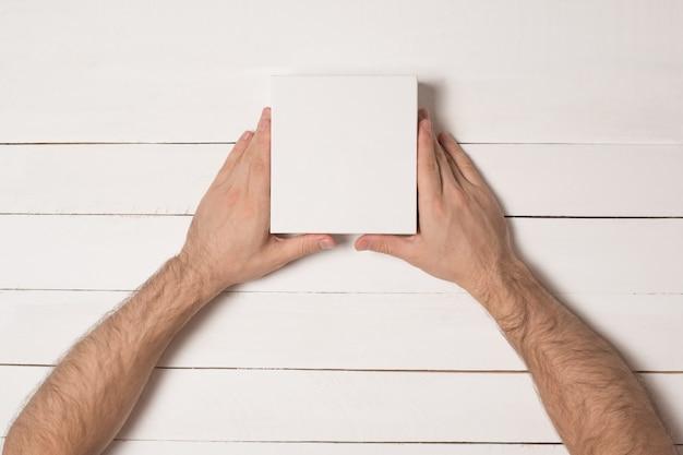 Pequenas caixas de papelão brancas nas mãos masculinas.