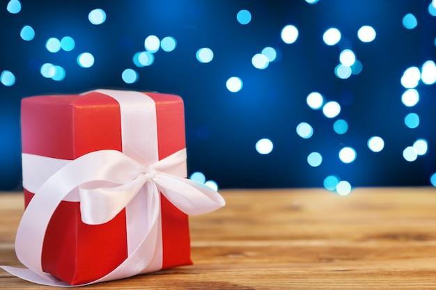 Pequenas caixas de presente de natal na mesa de madeira contra fundo de luzes de bokeh
