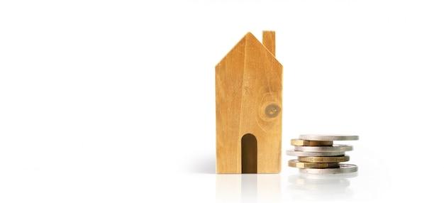Pequenas casas de pé nas pilhas de moedas. conceito de economia de investimento