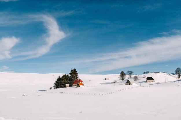 Pequenas casas em uma área montanhosa no inverno na neve contra um céu azul com nuvens cirros