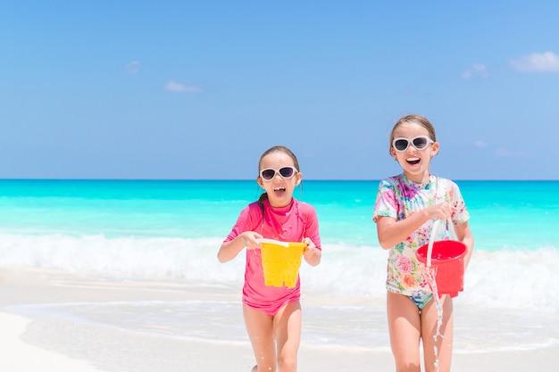 Pequenas crianças felizes se divertem muito na praia tropical jogando juntos