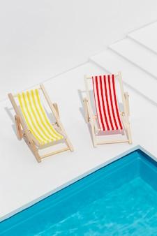 Pequenas espreguiçadeiras de ângulo alto ao lado da piscina