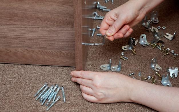 Pequenas ferramentas para montagem de móveis, suportes e fixação de móveis, close-up aperte o parafuso à mão usando uma chave allen.