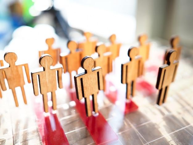 Pequenas figuras de pessoas de brinquedo de madeira estão na fila