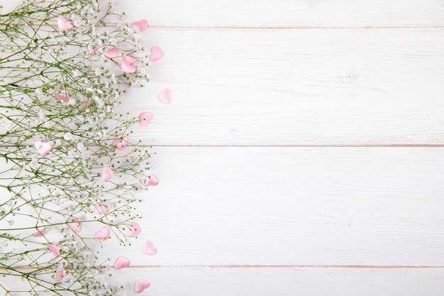 Pequenas flores brancas com corações rosa em um fundo branco de madeira, dia dos namorados ou dia das mães