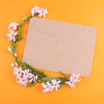 Pequenas flores com folhas verdes e papel em branco